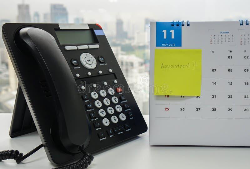 VOIP-IP-Telefon für die Telefonkonferenz, die im November Kalender mit klebriger Anmerkung der Verabredungsanzeige auf Schreibtis stockfotografie