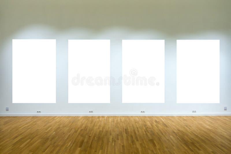 Voir les mes autres travaux dans le portfolio Quatre affiches en blanc sur le mur dans l'intérieur de galerie images libres de droits