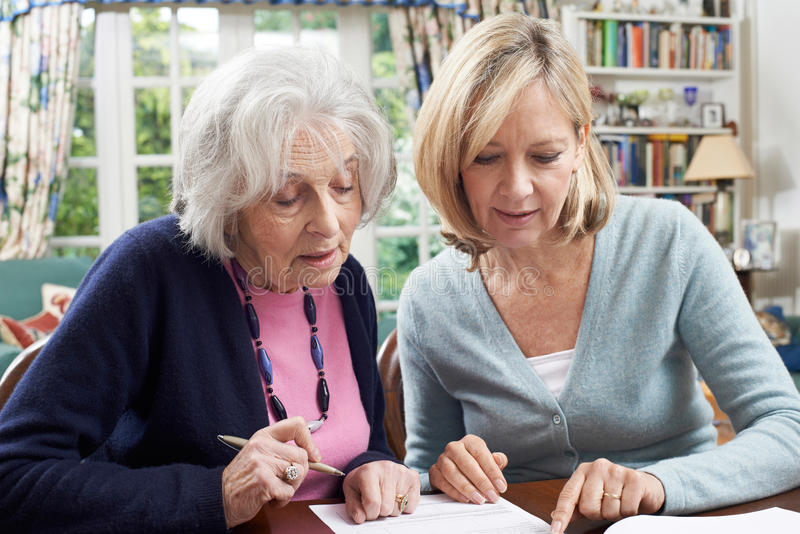 Voisin féminin aidant la femme supérieure à remplir le formulaire image libre de droits
