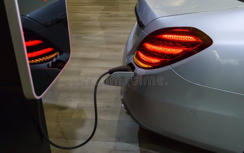 Voiture électrique avec branché un cable électrique à la station de charge photo libre de droits
