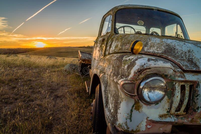 Voiture abandonnée d'épave dans un domaine dans l'Australie au coucher du soleil photos libres de droits