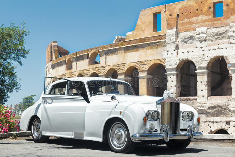 Voiture blanche de mariage de vintage classique fond de mur à bâtiment célèbre de Colosseum ou de Colisé image libre de droits