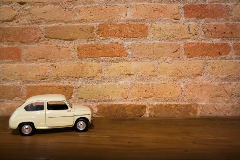 Voiture blanche de modèle de jouet rétro sur une surface en bois contre le mur de fond de brique rouge image libre de droits