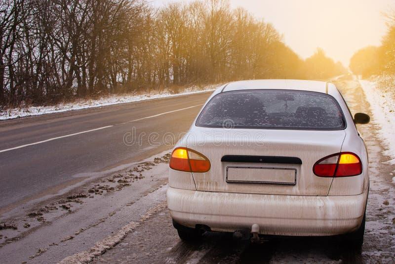 Voiture blanche sur le bord de la route pendant l'hiver avec les lumières d'arrêt avec la lumière du soleil photographie stock libre de droits
