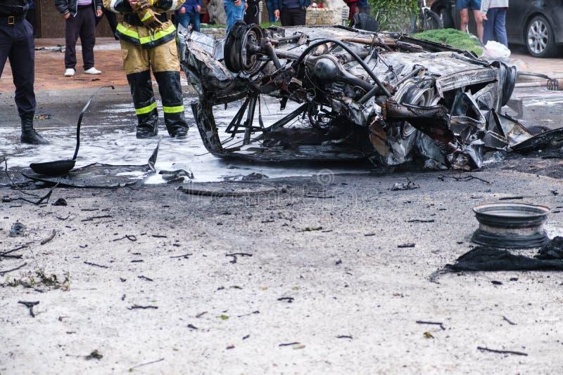 Voiture brûlée après un accident sur la route Sapeur-pompier se tenant tout près Photo de reportage d'accident photographie stock libre de droits