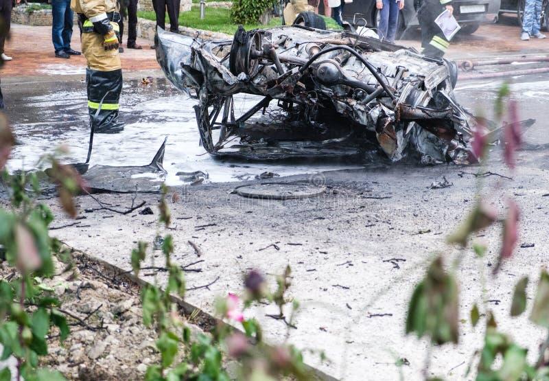 Voiture brûlée après un accident sur la route Sapeurs-pompiers se tenant tout près Photo de reportage dans la rue photographie stock libre de droits