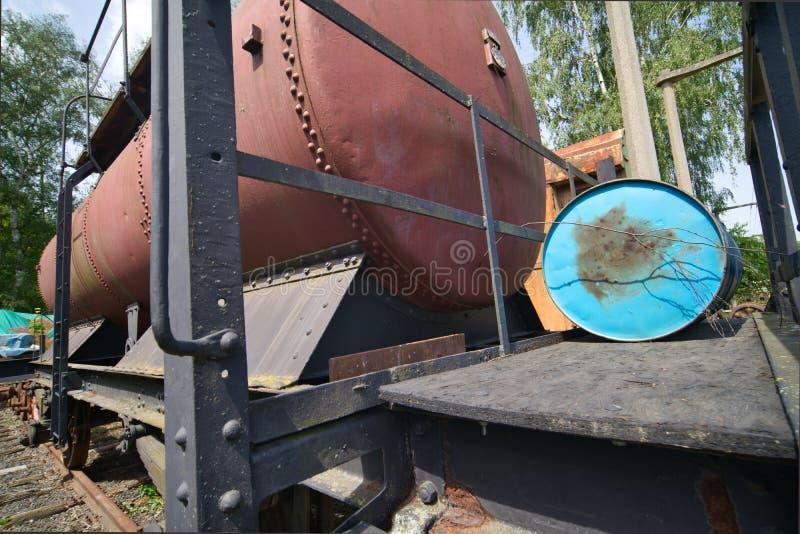 Voiture-citerne rouge historique avec réservoir de liquides derrière une plate-forme de fer avec un baril de pétrole bleu images libres de droits