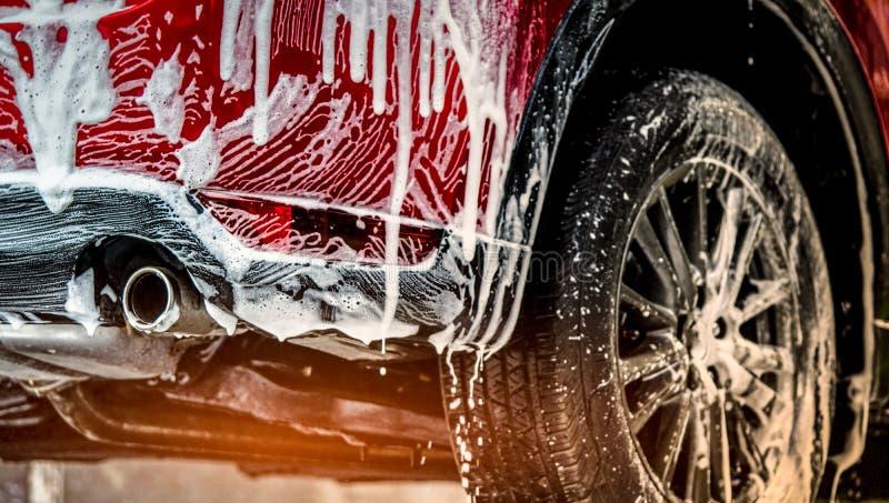 Voiture compacte rouge de SUV avec le sport et la conception moderne lavant avec du savon Voiture couverte de mousse blanche Conc photos stock