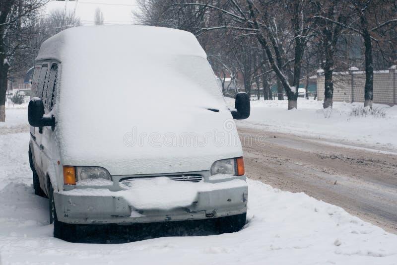 Voiture couverte de neige blanche dans la ville Minibus sous la neige Neige fondue de verglas, bâche de glace sur les routes, et  image libre de droits