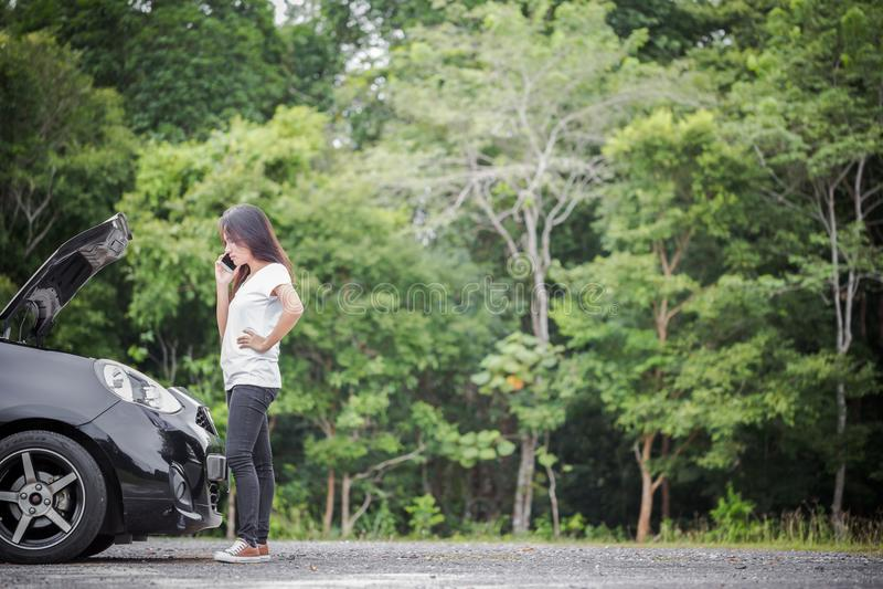 Voiture décomposée et femme asiatique appelle le mécanicien de voiture image libre de droits