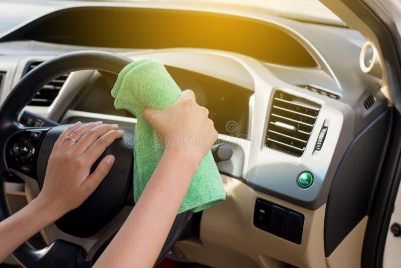 Voiture détaillant, femme de main nettoyant le tableau de bord sale de voiture avec le tissu de Microfiber image stock