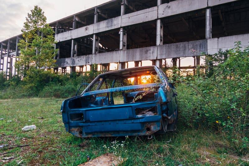 Voiture détruite et bâtiment industriel ruiné abandonné sur le fond de coucher du soleil image stock