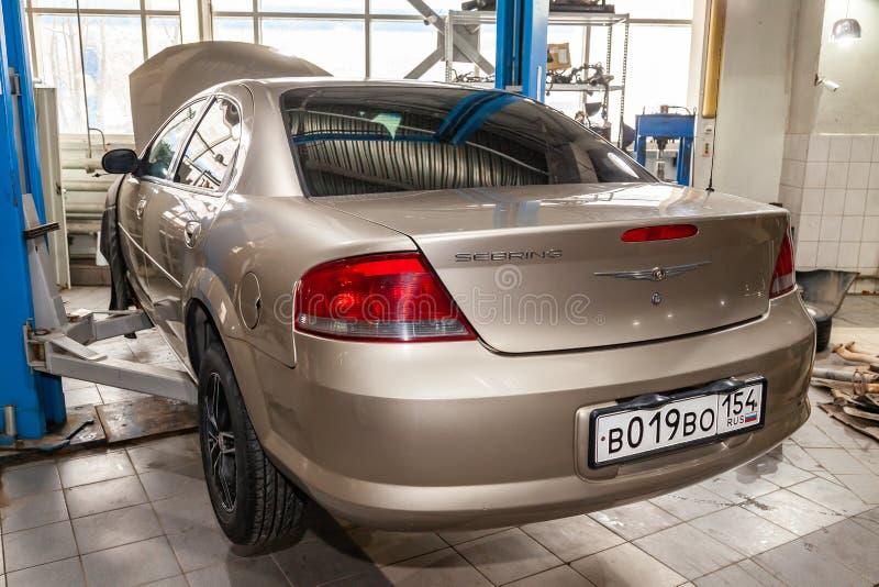 Voiture d'occasion beige avec un capot ouvert augmenté sur un ascenseur pour réparer le châssis et le moteur dans un atelier de r photo stock