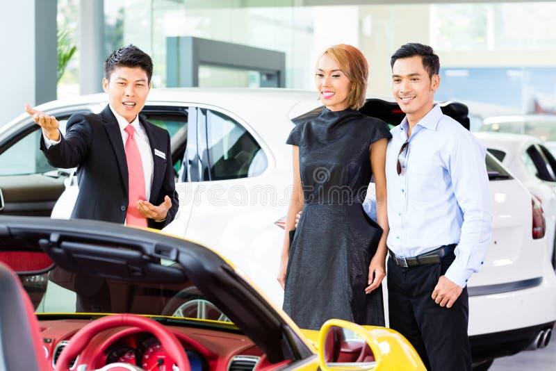 Voiture de achat de couples asiatiques au concessionnaire image stock