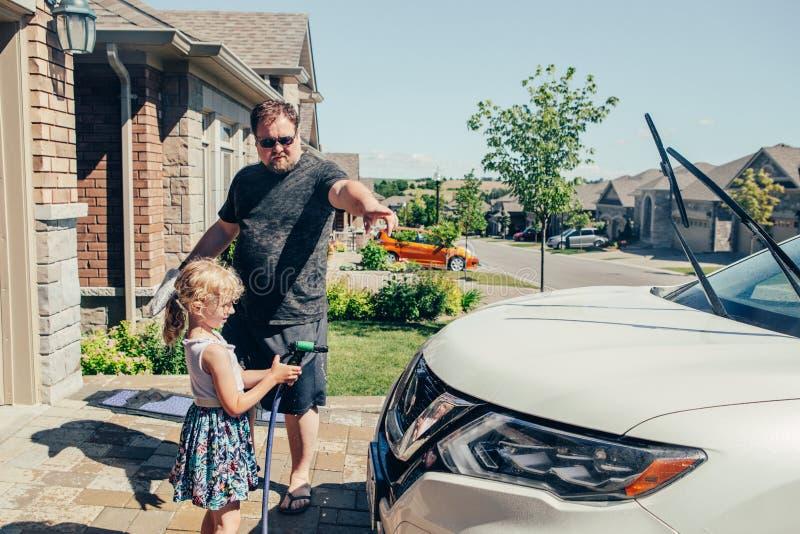Voiture de aide de lavage de père de fille sur l'allée dans la maison avant le jour d'été photo stock