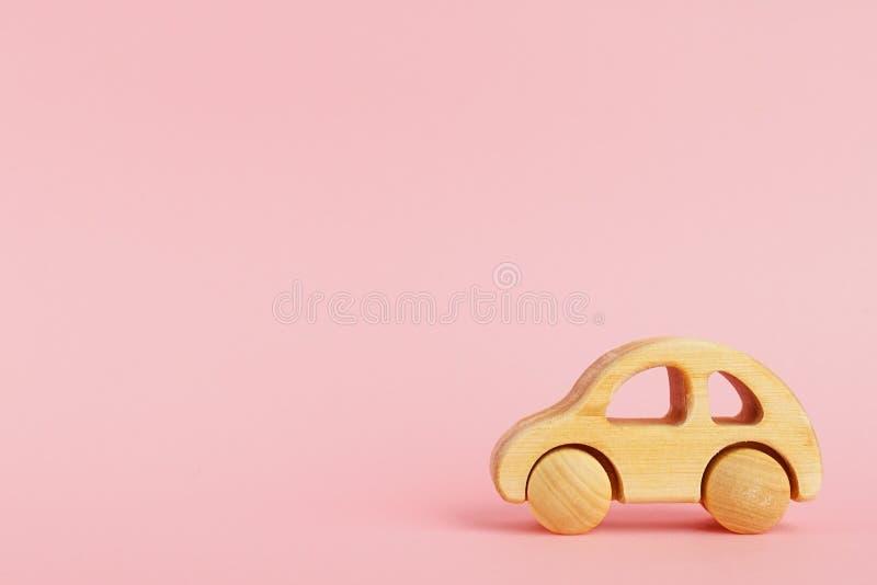 Voiture de bébé en bois sur un fond en pastel rose avec le copyspace photographie stock libre de droits