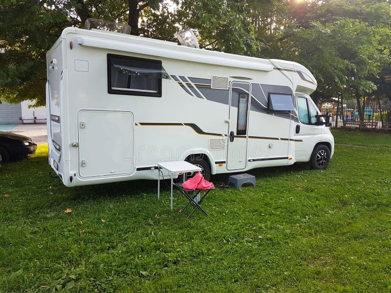 Voiture de caravane sur l'herbe verte campante et tresse près de lac photo stock