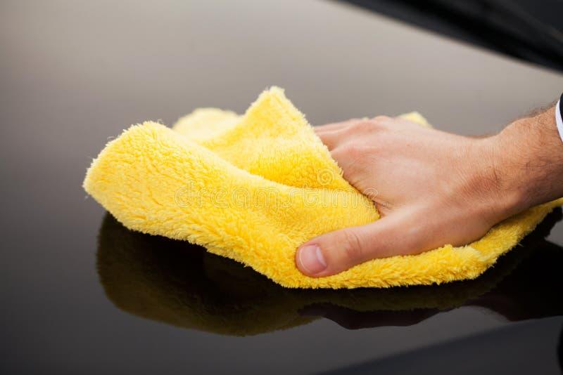 Voiture de Clining Essuyage du panneau d'une voiture de luxe avec le microfiber jaune, vue en gros plan photographie stock
