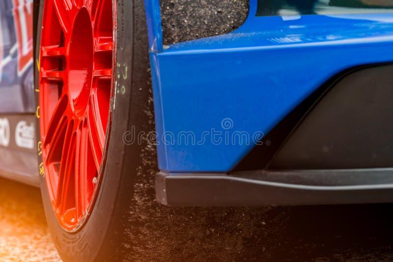 Voiture de course bleue avec la roue et le pneu de sport de haute performance Le pneu de voiture de sport avec le sable et le sol image stock
