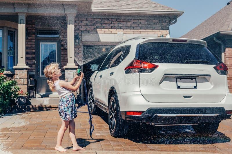 voiture de lavage de fille sur l'allée dans la maison avant le jour ensoleillé d'été images stock