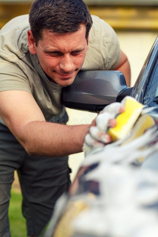 Voiture de lavage masculine de lavage de voiture de dimanche avec une éponge et une mousse images stock