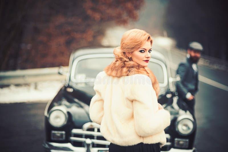 Voiture de limousine avec le conducteur et la dame sexy dans le manteau de fourrure voiture de limousine dans le rétro style avec image libre de droits