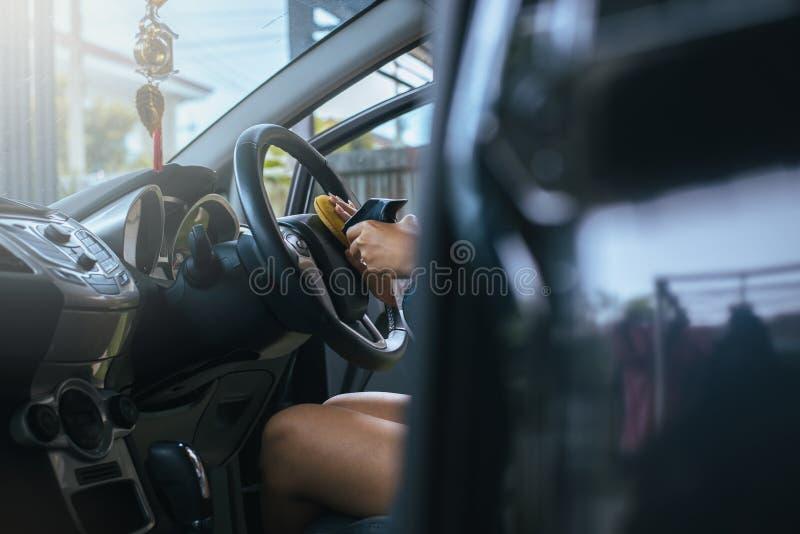 Voiture de nettoyage de main-d'œuvre féminine à l'intérieur de tableau de bord, utilisant le poli de application cireux dans la v photo libre de droits