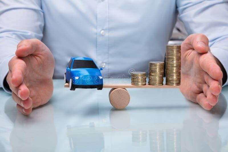 Voiture de Protecting Balance Between d'homme d'affaires et pièces de monnaie empilées images libres de droits