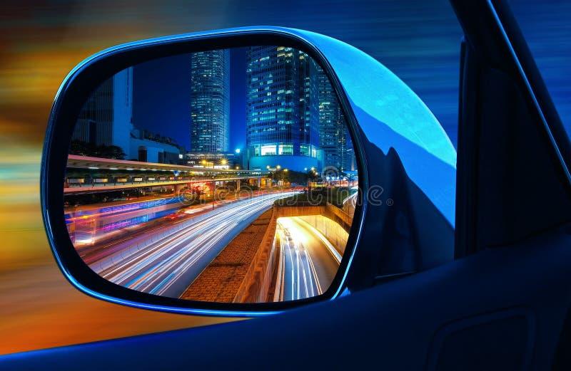 Voiture de rétroviseur de plan rapproché à toute allure la nuit dans la grande métropole avec des gratte-ciel images libres de droits