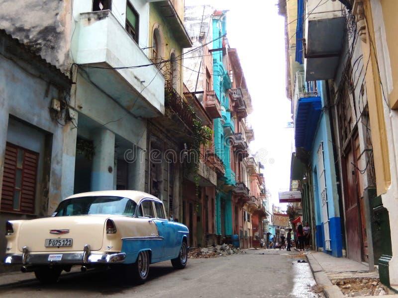 VOITURE DE VINTAGE DANS UNE RUE AVEC LES FAÇADES COLORÉES, LA HAVANE, CUBA image libre de droits