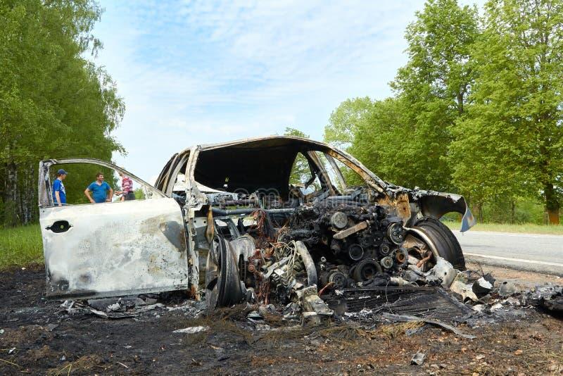 Voiture entièrement brûlée sur le bord de la route après collision avec le camion lourd images libres de droits