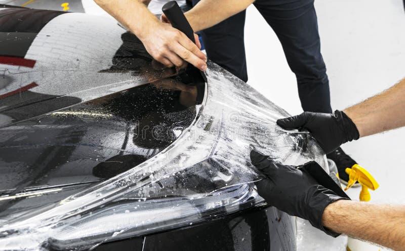 Voiture enveloppant le spécialiste mettant l'aluminium ou le film de vinyle sur la voiture Film protecteur sur la voiture Appliqu photographie stock libre de droits