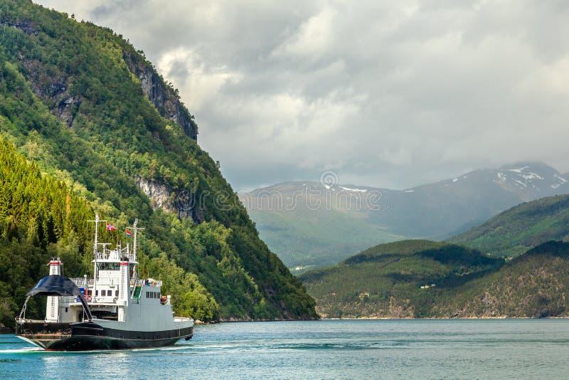 Voiture et ferry-boat transportant des passagers croisant le fjord avec le paysage de montagne à l'arrière-plan, Tafjord, plus de image stock