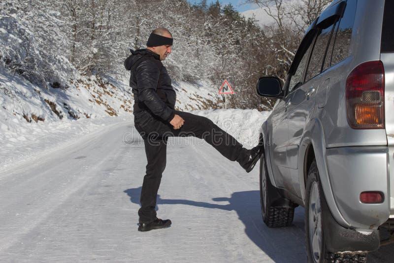 Voiture et homme sur la route neigeuse Voiture cassée proche humaine en hiver images stock