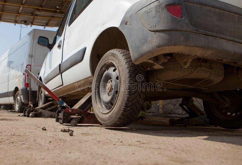 Voiture fixe dans le garage, ascenseur de cric hydraulique de plancher une voiture, roue sans pneu image libre de droits