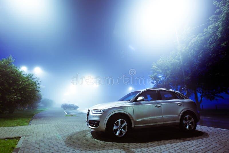 Voiture garée sur une rue de ville de nuit couverte de brouillard, ville brouillée images stock