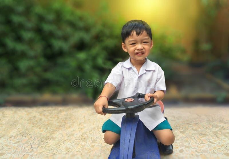 Voiture heureuse de jouet d'entraînement de petit garçon Enfant espiègle au terrain de jeu photographie stock libre de droits