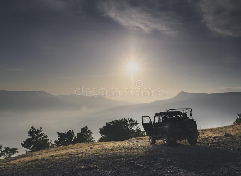 Voiture hors route sur le sommet de la montagne au lever ou au coucher du soleil photo stock