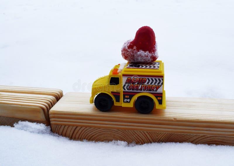 Voiture jaune de jouet portant le coeur fait maison de platicine photo stock
