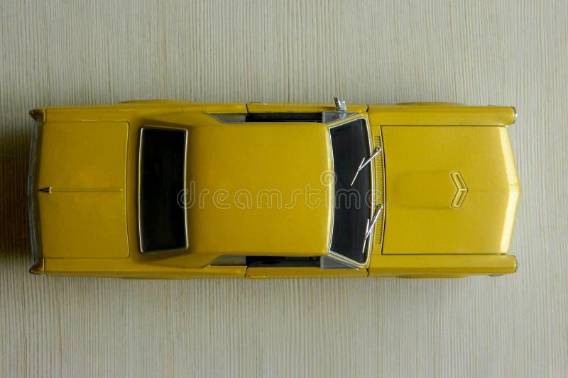 Voiture jaune de jouet sur la surface rayée grise Modèle de voiture classique de muscle avec les ombres et le foyer partiellement image stock