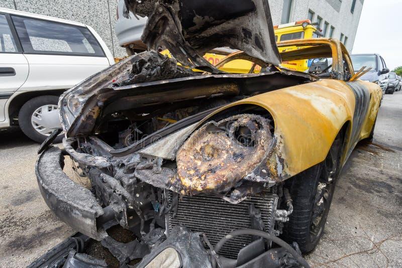 Voiture jaune de sport écrasée et brûlée photographie stock libre de droits