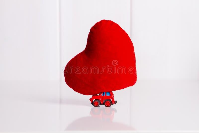 Voiture miniature portant un coussin rouge de coeur photos libres de droits