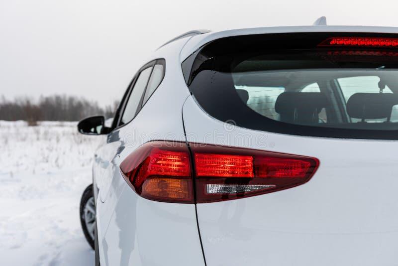 Voiture moderne blanche avec les feux de freinage allumés blanc d'isolement de vue arrière image stock