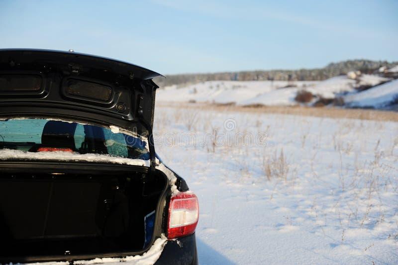 Voiture noire avec le tronc ouvert sur une route de campagne russe de neige d'hiver Village à l'arrière-plan Ciel bleu image stock