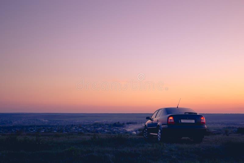 Voiture noire dans le domaine au coucher du soleil photo libre de droits