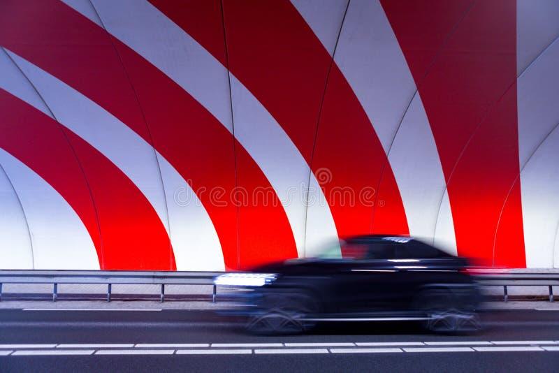 Voiture noire motrice rapide dans le tunnel avec des rayures image stock