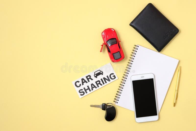Voiture partageant le concept de service Voiture rouge de jouet, accord, cl? de v?hicule, smartphone, permis de conduire automati photos libres de droits