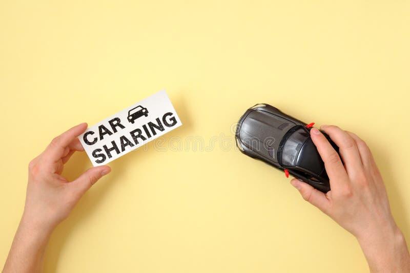 Voiture partageant le concept Mains humaines tenant le mod?le de voiture de jouet et le signe des textes photos stock