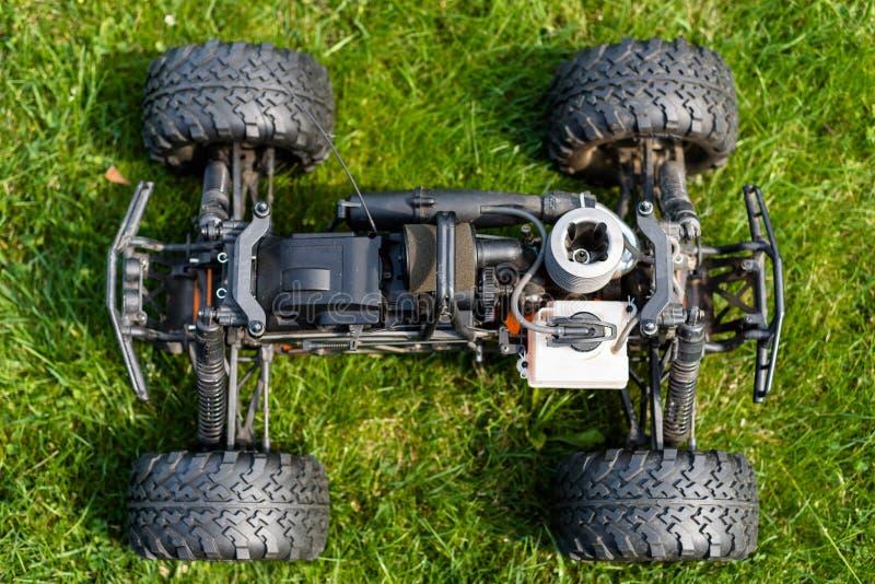 Voiture radioguidée avec le moteur à combustion interne pour le carburant nitro, avec un cylindre, se tenant sur l'herbe verte images libres de droits