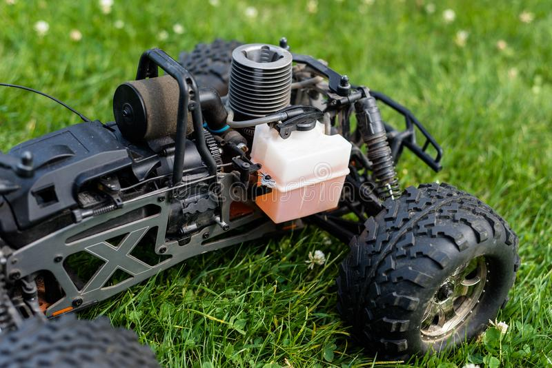 Voiture radioguidée avec le moteur à combustion interne pour le carburant nitro, avec un cylindre, se tenant sur l'herbe verte photos libres de droits